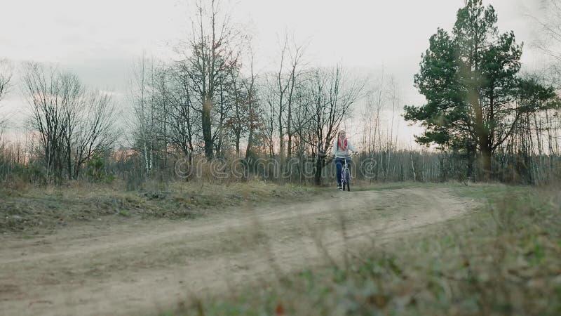 Jonge mooie vrouw die een fiets in een park berijden Actieve mensen outdoors
