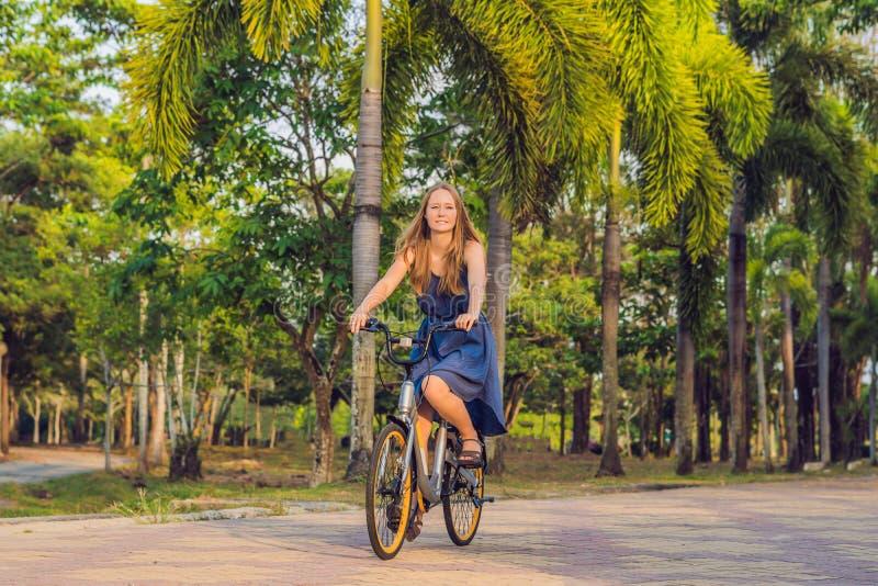 Jonge mooie vrouw die een fiets in een park berijden Actieve mensen openlucht royalty-vrije stock afbeeldingen