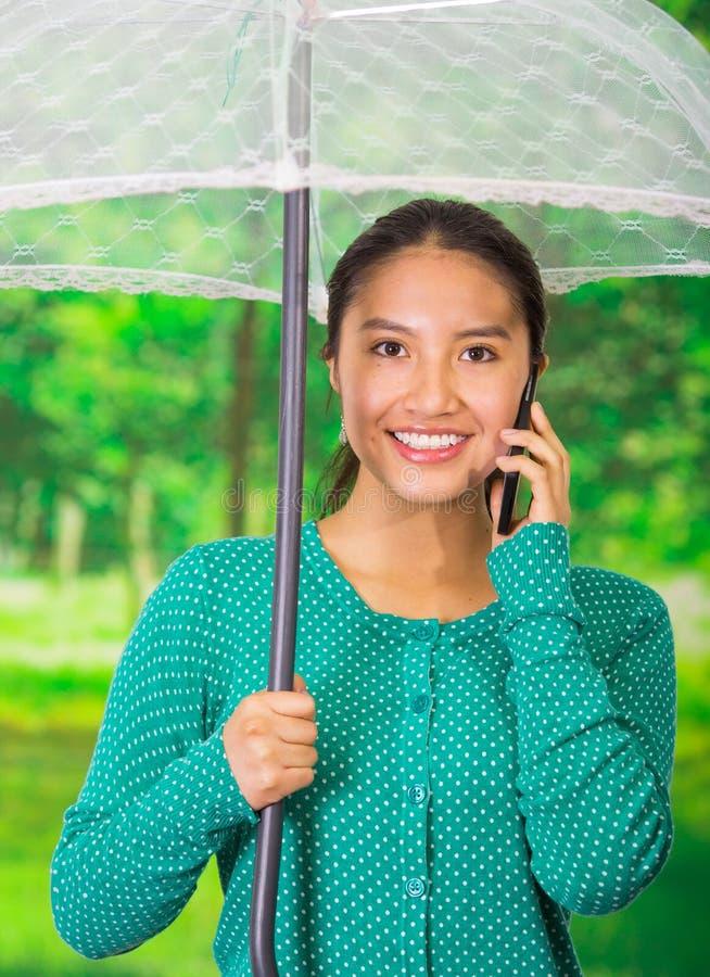 Jonge mooie vrouw die een groene sweater met paraplu dragen bij mooi autumpark, die haar mobiele telefoon met behulp van royalty-vrije stock afbeelding