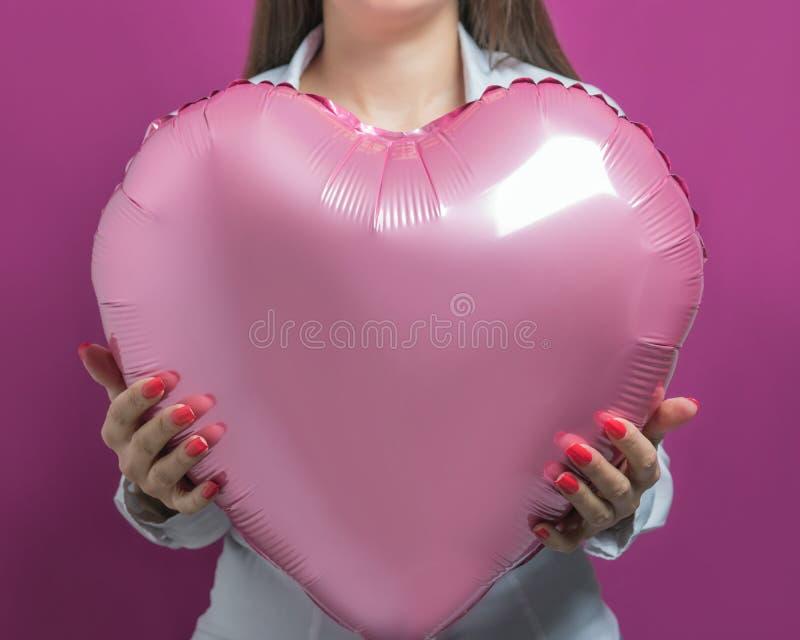 Jonge mooie vrouw die een hart gevormde luchtballon houden De dagconcept van de valentijnskaart ` s stock afbeelding