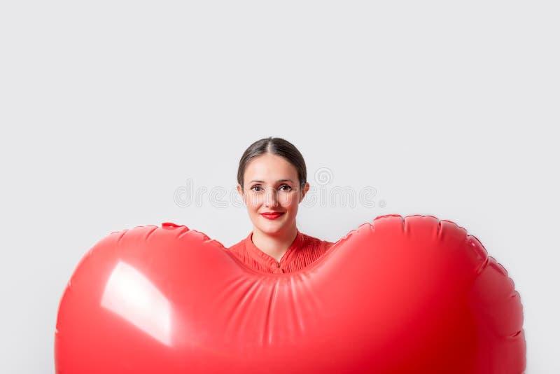 Jonge mooie vrouw die een hart gevormde luchtballon houden De dagconcept van de valentijnskaart ` s royalty-vrije stock fotografie