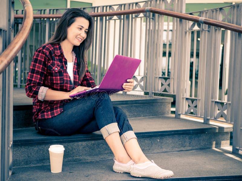 Jonge mooie vrouw die een laptop computer met behulp van bij openlucht stock fotografie