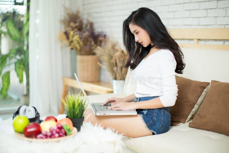 Jonge mooie vrouw die een laptop computer met behulp van stock foto's