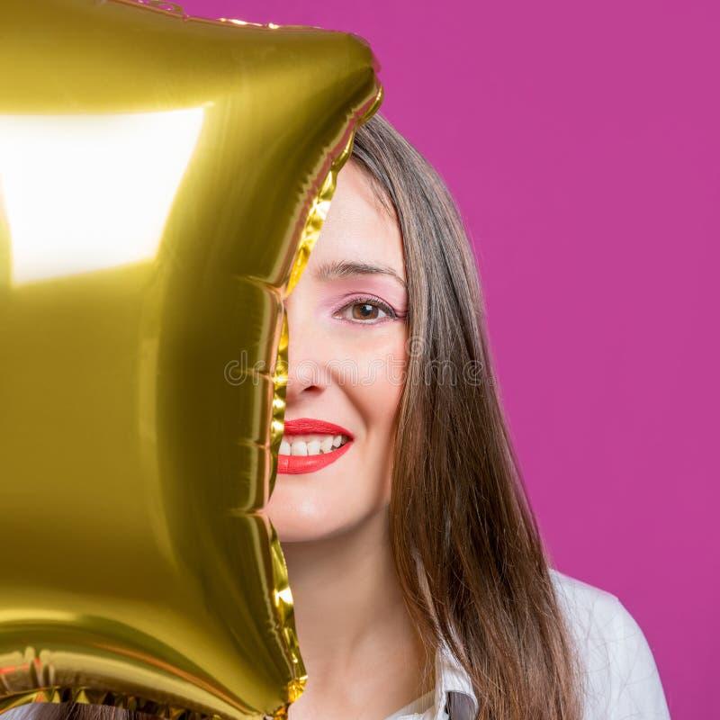 Jonge mooie vrouw die een ster gevormde ballon houden Het concept van de vakantie royalty-vrije stock foto's