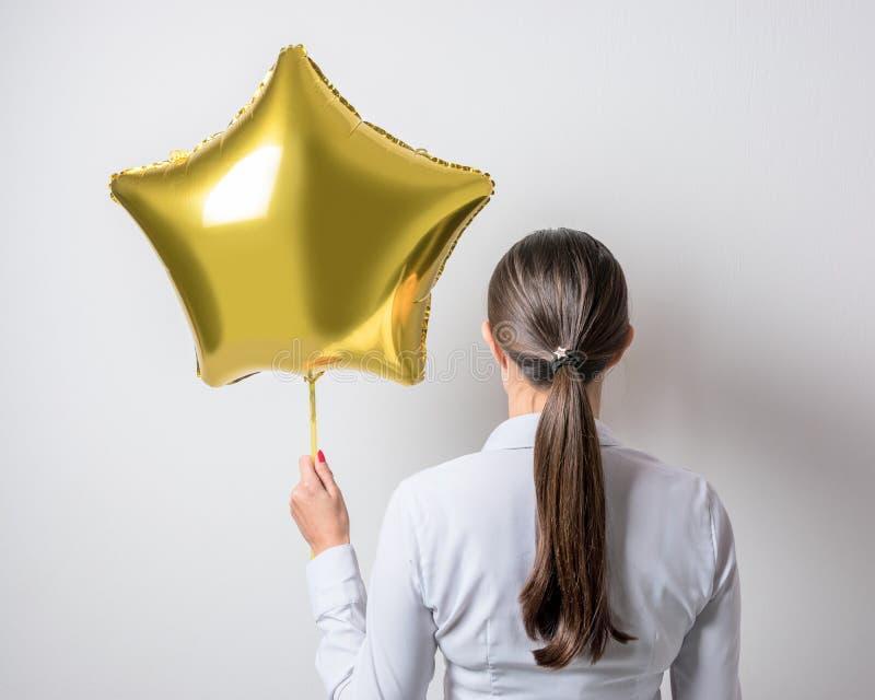 Jonge mooie vrouw die een ster gevormde ballon houden Het concept van de vakantie stock fotografie