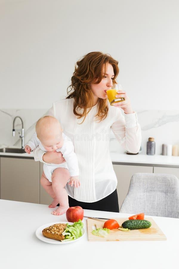 Jonge mooie vrouw die en haar bevinden zich houden weinig baby terwijl het drinken van sap en het koken op keuken royalty-vrije stock fotografie