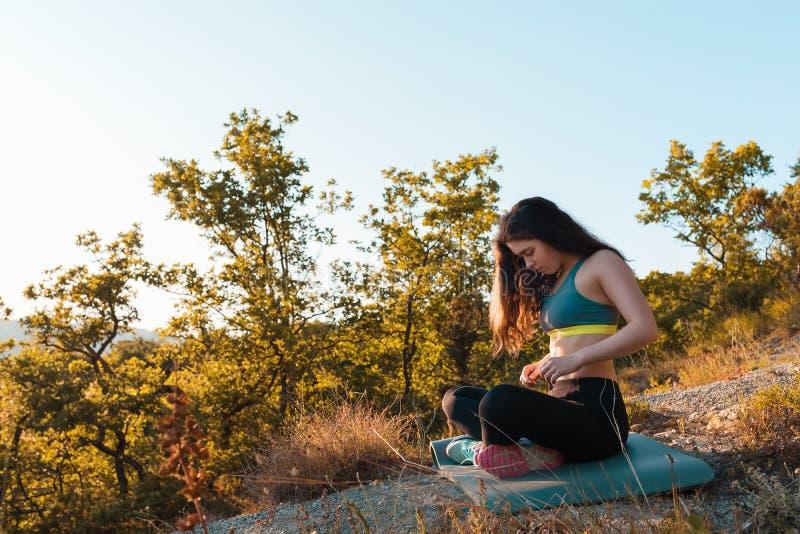 Jonge mooie vrouw die en in het Park rusten opwarmen Het concept yoga, sporten en meditatie De ruimte van het exemplaar stock foto