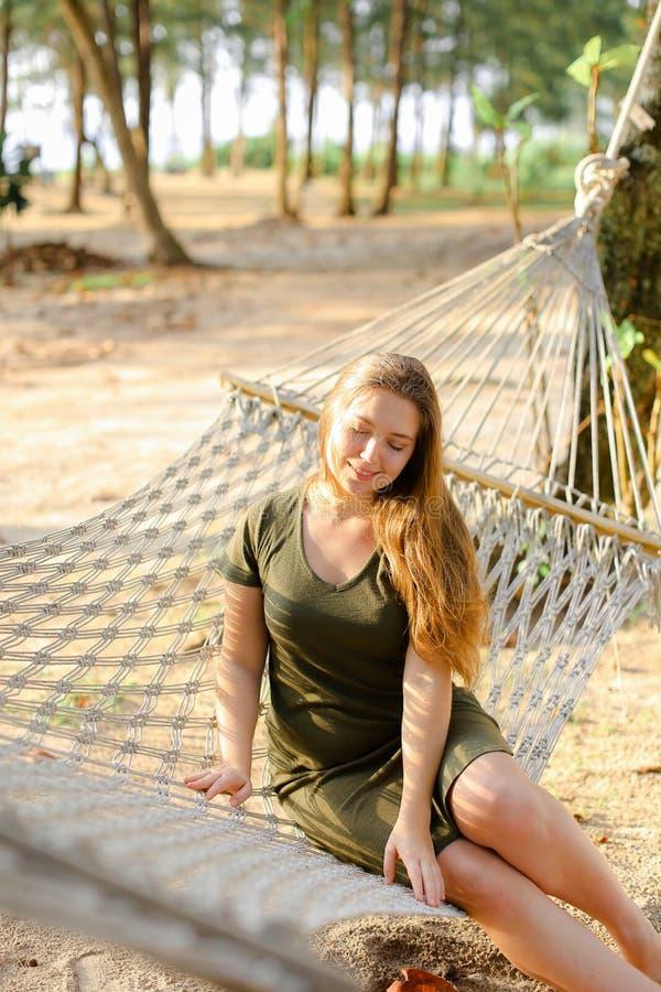 Jonge mooie vrouw die groene kledingszitting op rieten hangmat met zand en palmen op achtergrond dragen stock fotografie