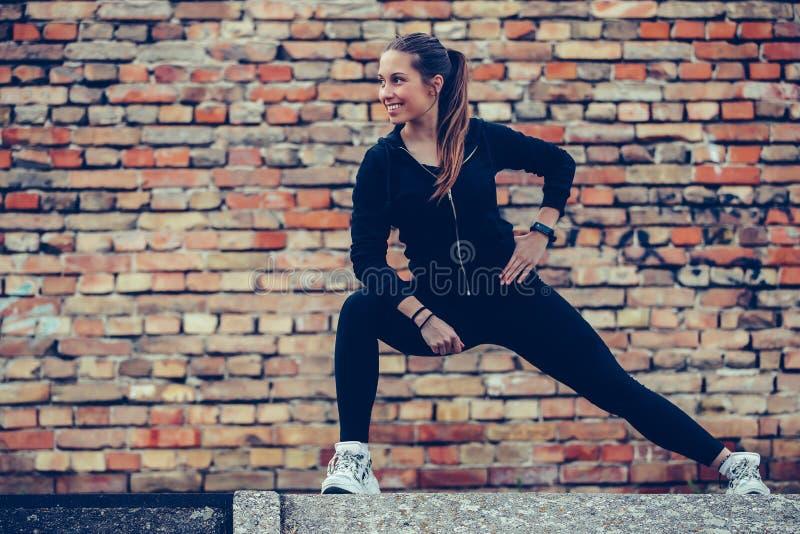 Jonge mooie vrouw die haar benen uitrekken, bakstenen muur op de achtergrond stock foto