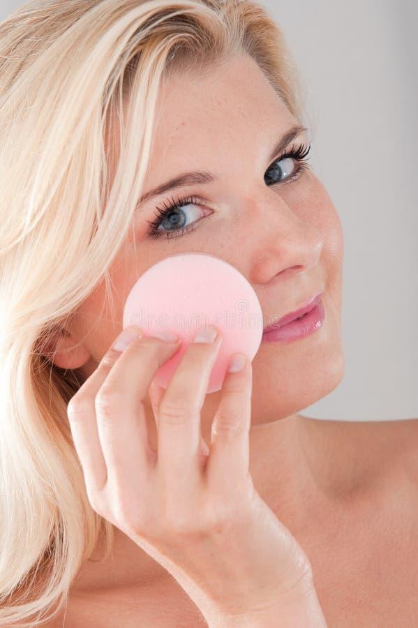 Jonge mooie vrouw die haar gezicht reinigt royalty-vrije stock afbeelding