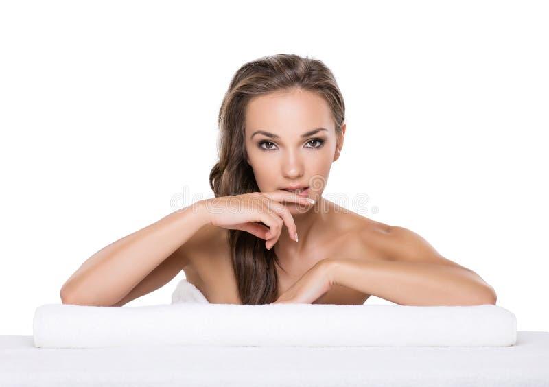 Jonge mooie vrouw die haar handen rusten op een handdoek in kuuroordsalon stock foto