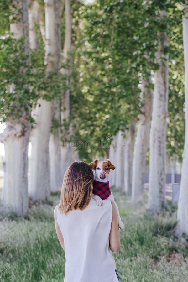 Jonge mooie vrouw die haar leuke kleine hond op schouder houden outdoors Liefde voor dierenconcept en levensstijl in openlucht stock fotografie