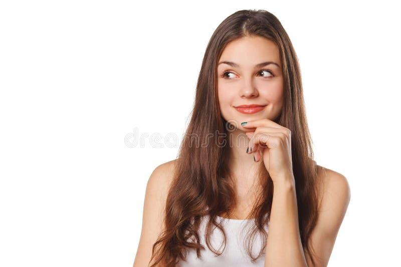 Jonge mooie vrouw die het bekijken aan de kant lege die exemplaarruimte denken, over witte achtergrond wordt geïsoleerd stock afbeeldingen