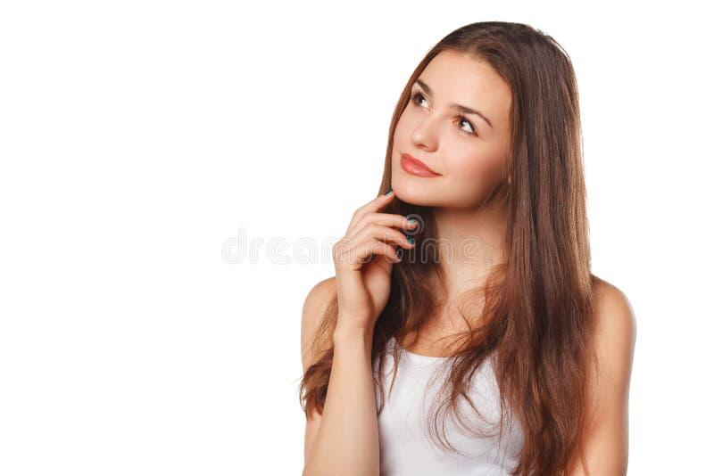 Jonge mooie vrouw die het bekijken aan de kant lege die exemplaarruimte denken, over witte achtergrond wordt geïsoleerd royalty-vrije stock afbeeldingen
