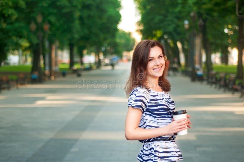 Jonge mooie vrouw die in het park met de koffie in haar blijven stock afbeeldingen