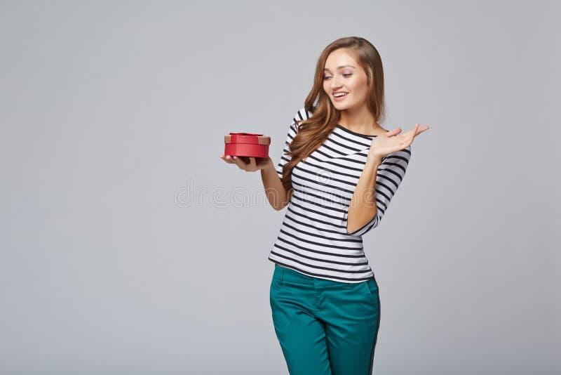 Jonge mooie vrouw die kleine rode doos houden Studioportret  stock foto's