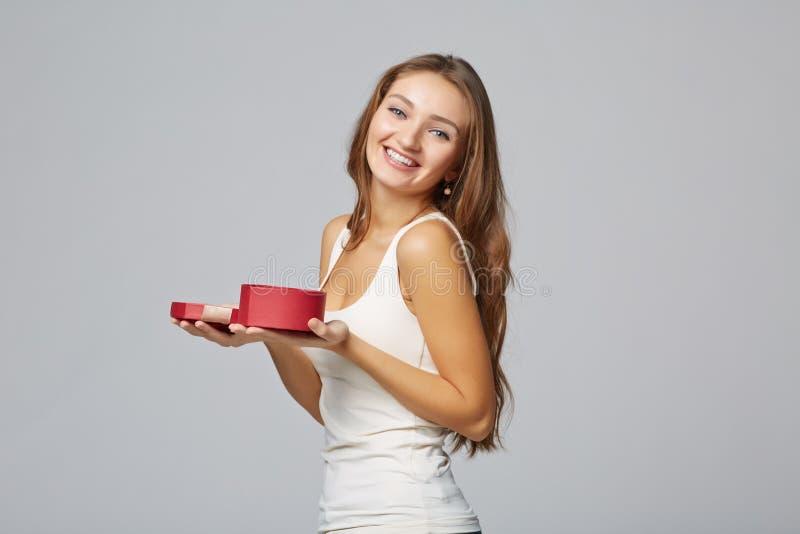 Jonge mooie vrouw die kleine rode doos houden Studioportret  stock foto