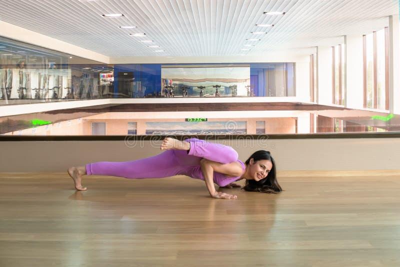 Jonge mooie vrouw die lilac sportkleding dragen die aga uitwerken stock foto's