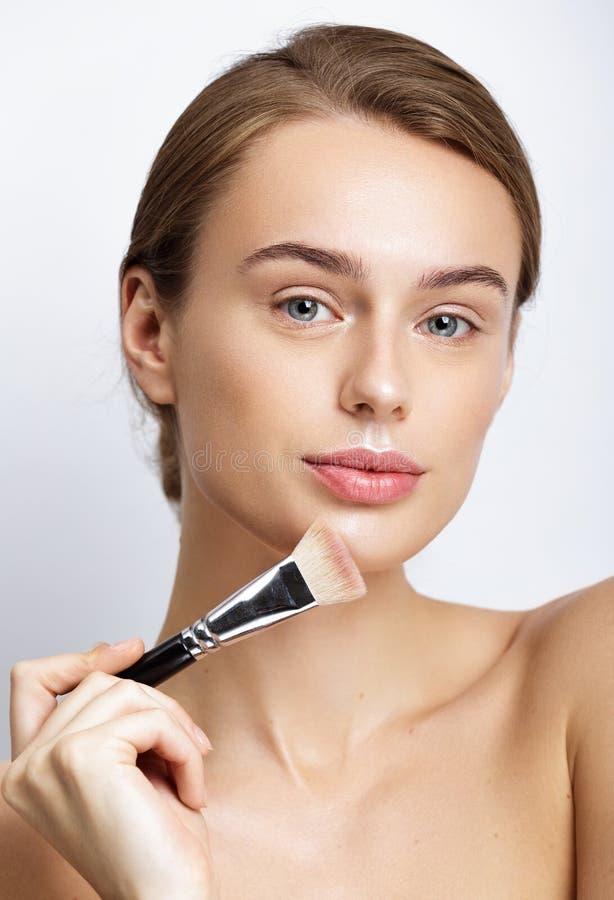 Jonge mooie vrouw die make-up op gezicht toepassen stock afbeelding