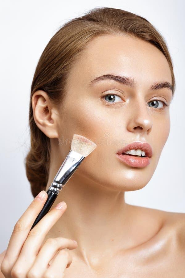 Jonge mooie vrouw die make-up op gezicht toepassen stock afbeeldingen