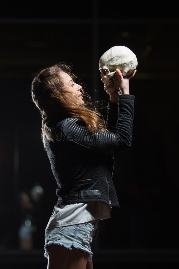 Jonge mooie vrouw die menselijke schedel in openlucht houdt royalty-vrije stock afbeeldingen