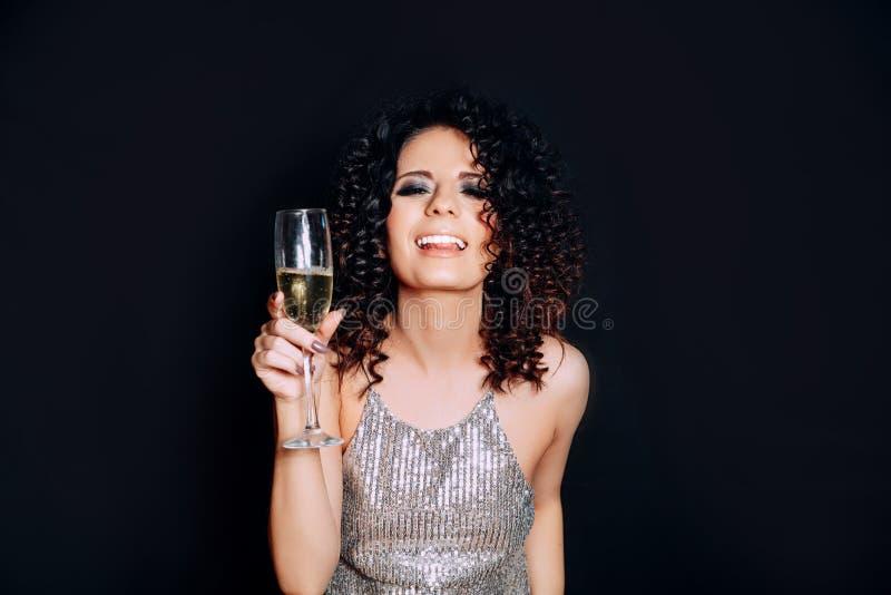 Jonge mooie vrouw die met glas champagne en het glimlachen dansen Het meisje is gelukkig over het Nieuwjaar royalty-vrije stock fotografie