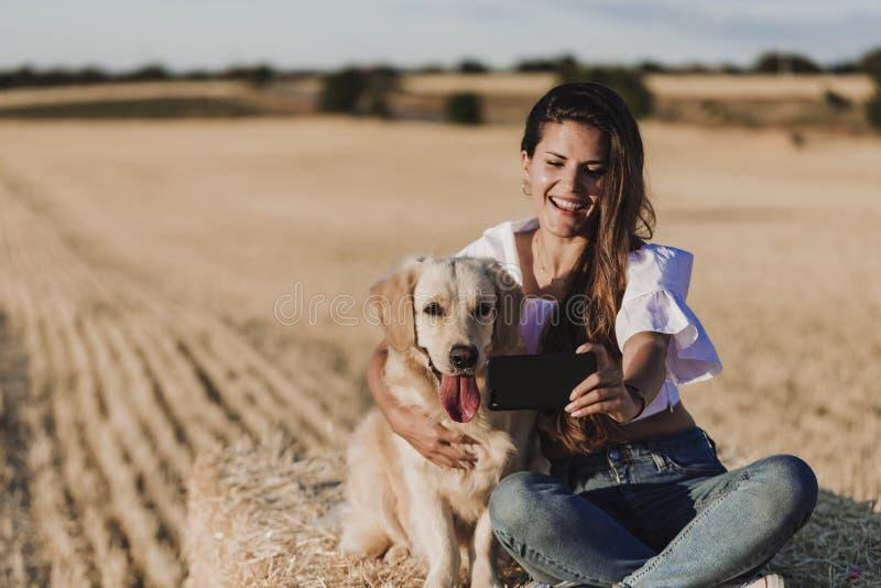 Jonge mooie vrouw die met haar golden retrieverhond op een geel gebied bij zonsondergang lopen Aard en levensstijl in openlucht stock afbeelding