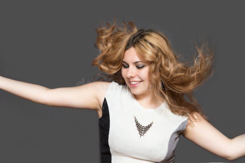 Jonge mooie vrouw die met lange bruine haarsprongen binnen glimlachen stock afbeeldingen