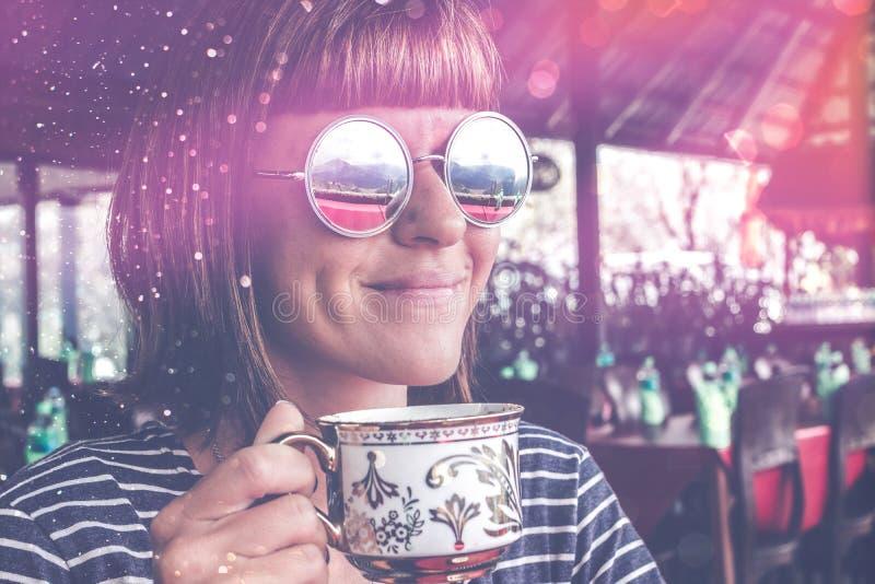 Jonge mooie vrouw die met zonnebril koffie in restaurant buiten terras drinken Het eiland van Bali stock fotografie
