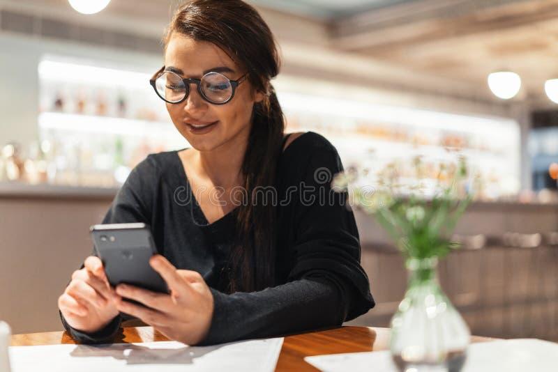 Jonge mooie vrouw die mobiele telefoon in handen houden terwijl het wachten op haar maaltijd royalty-vrije stock afbeeldingen