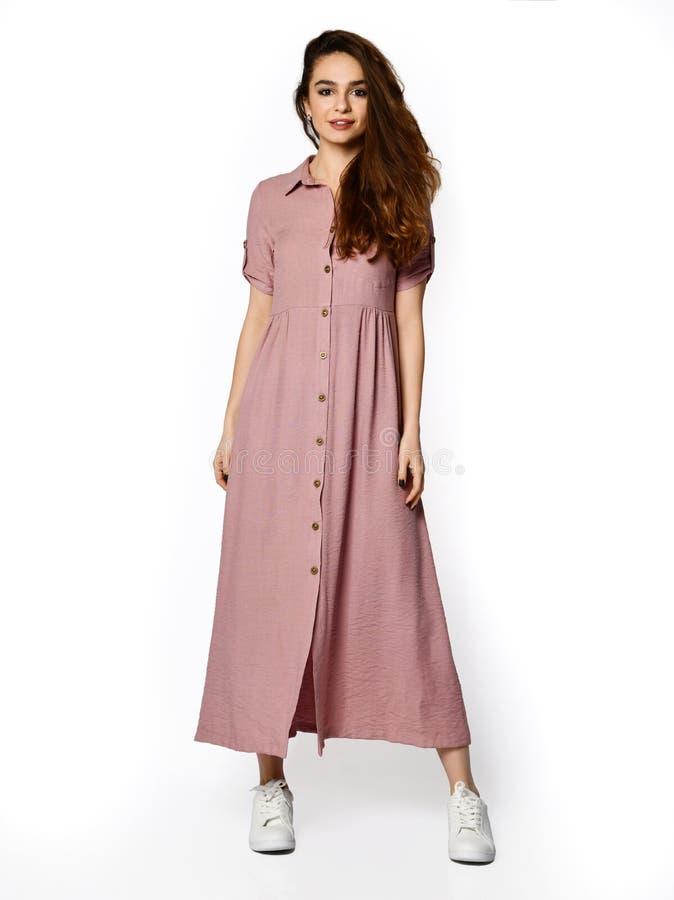 Jonge mooie vrouw die in nieuw lang de kledings volledig lichaam van de ontwerp toevallig zomer lopen op wit stock foto