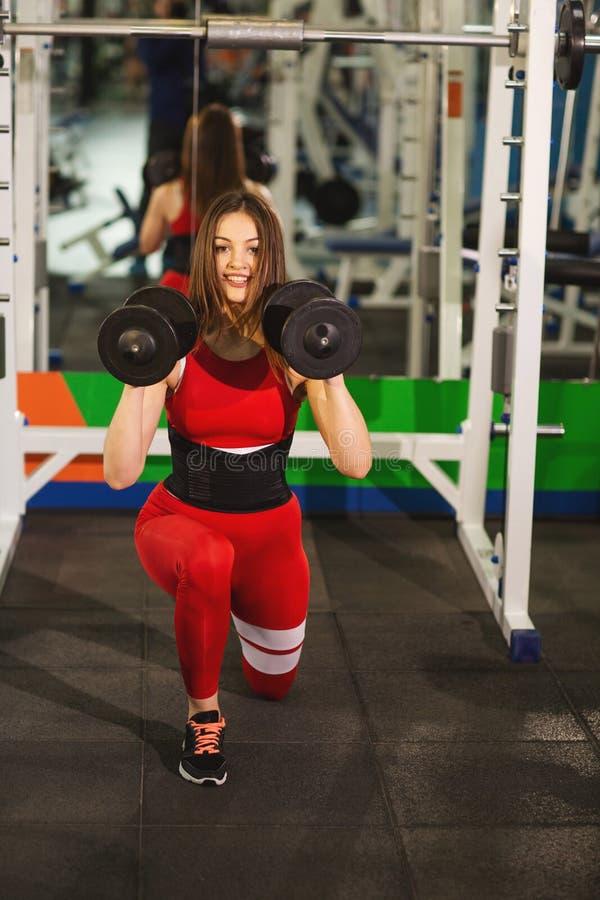 Jonge mooie vrouw die oefeningen met domoor in gymnastiek doen Het blije glimlachende meisje geniet van met haar opleidingsproces stock afbeelding
