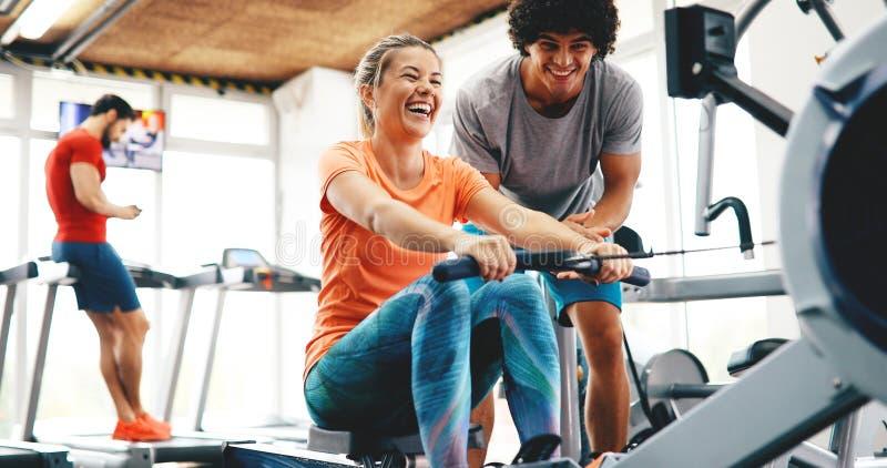 Jonge mooie vrouw die oefeningen met persoonlijke trainer doen stock afbeelding