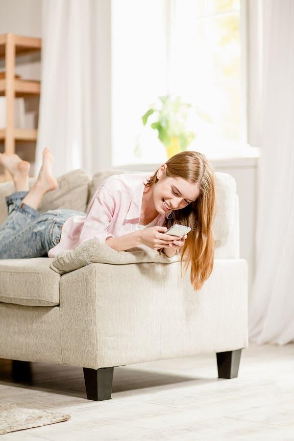 Jonge mooie vrouw die op bank sms op haar smartphone schrijven stock afbeelding