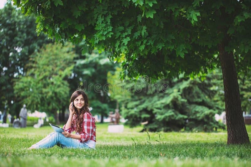 Jonge mooie vrouw die op de telefoon in het park spreken stock foto