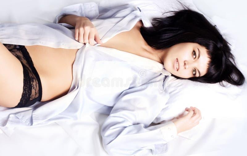 Jonge Mooie vrouw die op het bed ligt royalty-vrije stock foto's