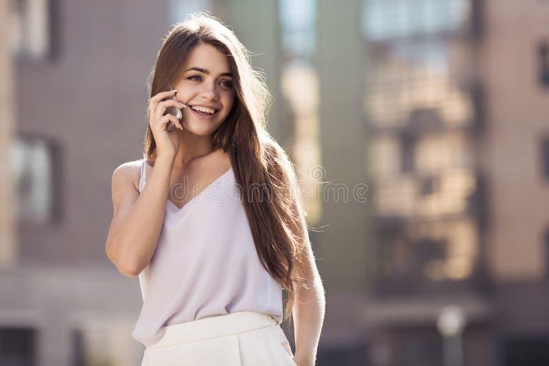 Jonge mooie vrouw die op mobiele telefoon spreekt royalty-vrije stock foto