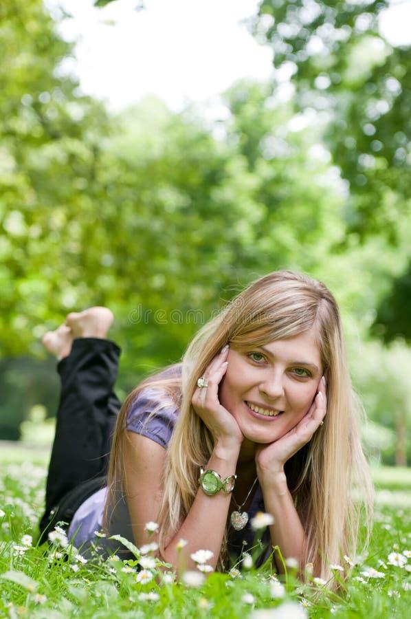 Jonge mooie vrouw die in openlucht ligt royalty-vrije stock fotografie