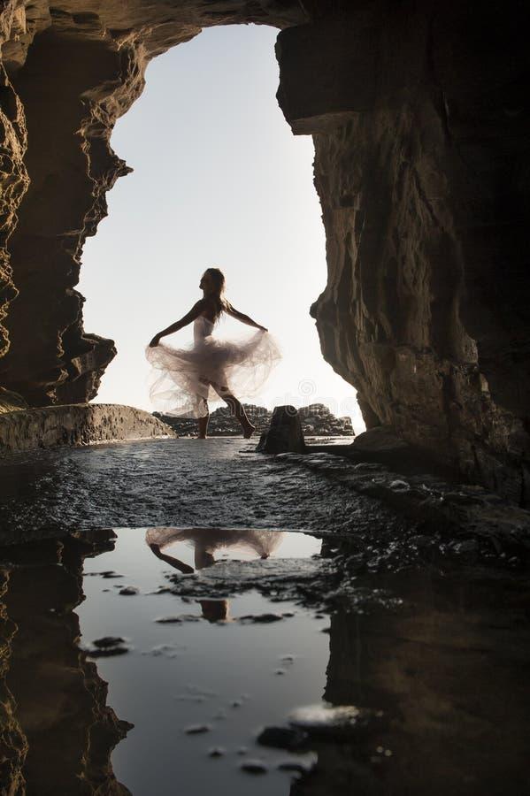 Jonge mooie vrouw die pret hebben die onder rotsoverwelfde galerij dansen stock foto's