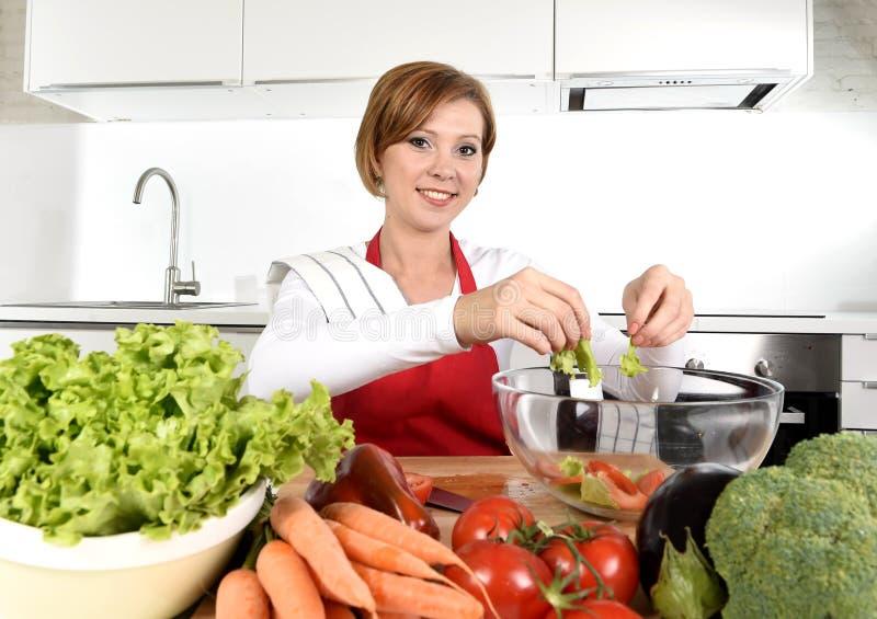 Jonge mooie vrouw die in rode schort thuis keuken het plantaardige saladekom gelukkig glimlachen voorbereiden royalty-vrije stock afbeeldingen
