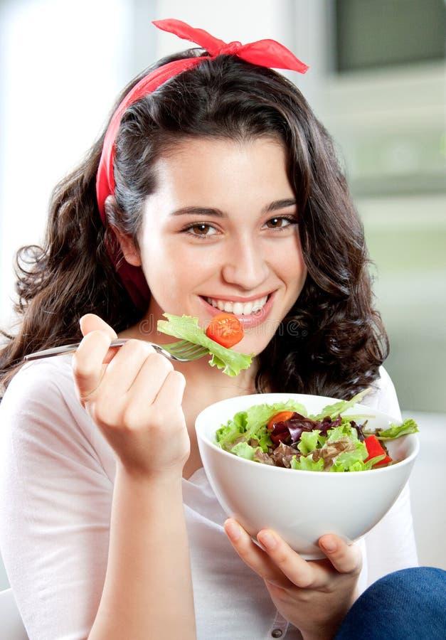 Jonge mooie vrouw die salade eten royalty-vrije stock afbeelding