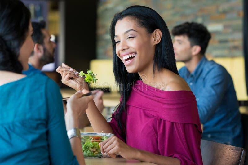 Jonge mooie vrouw die salade eten stock foto