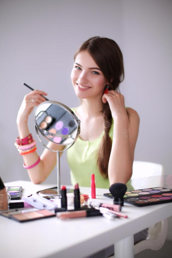 Jonge mooie vrouw die samenstelling maken dichtbij spiegel, die bij het bureau zitten stock fotografie