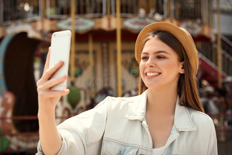 Jonge mooie vrouw die selfie dichtbij carrousel nemen stock afbeeldingen