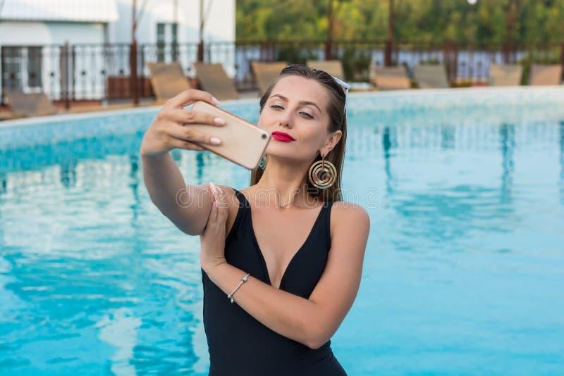 Jonge mooie vrouw die selfie op een smartphone in de pool doen royalty-vrije stock fotografie