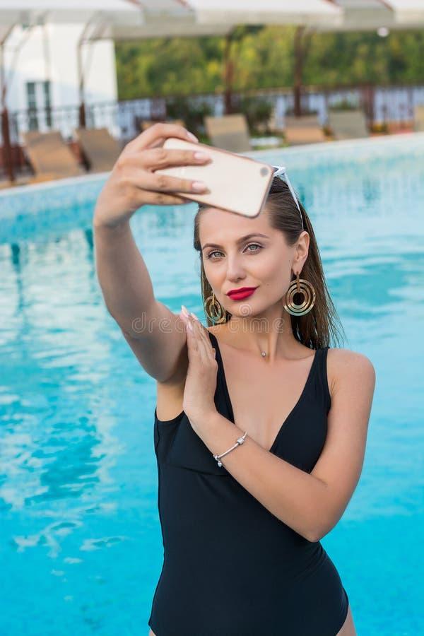 Jonge mooie vrouw die selfie op een smartphone in de pool doen royalty-vrije stock foto
