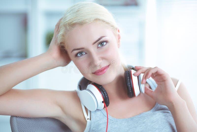 Jonge mooie vrouw die thuis op bank en het luisteren muziek zitten royalty-vrije stock foto