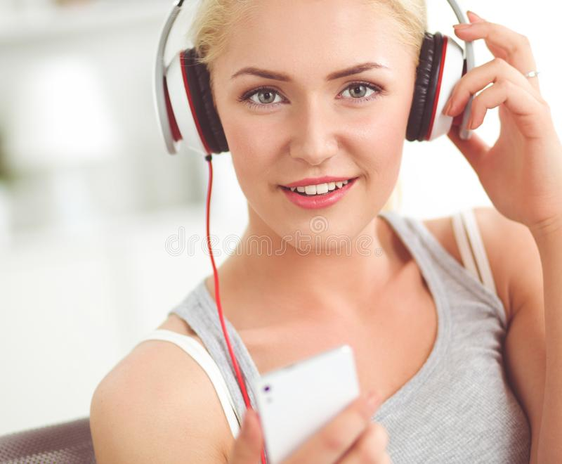 Jonge mooie vrouw die thuis op bank en het luisteren muziek zitten stock fotografie