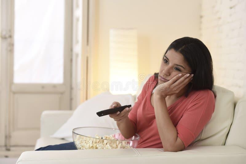 Jonge mooie vrouw die thuis vermoeid en bored op televisie letten royalty-vrije stock afbeeldingen