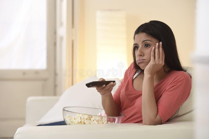 Jonge mooie vrouw die thuis vermoeid en bored op televisie letten stock afbeeldingen